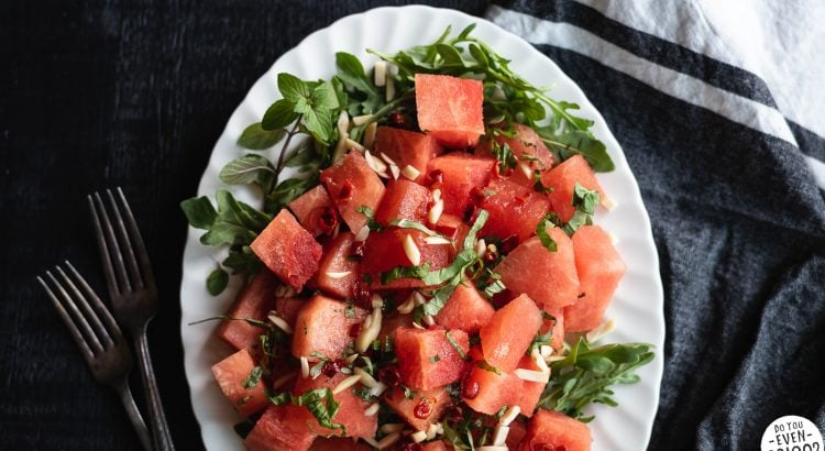 Watermelon Arugula Salad Recipe on oval white plate with linen in the background.