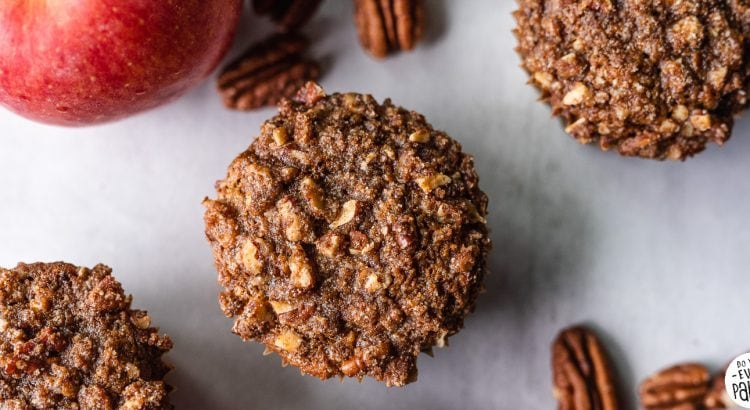 Picture of gluten free apple pecan streusel muffins recipe with pecans and an apple on a concrete background | DoYouEvenPaleo.net