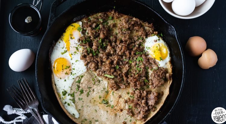 Sweet and Savory Dutch Baby Pancake Recipe in a cast iron skillet surrounded by eggs and linens on a dark background by DoYouEvenPaleo.net