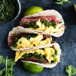 Paleo Steak and Egg Breakfast Tacos with Chimichurri on a dark background