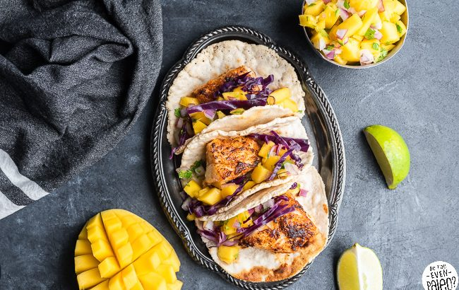 Paleo Fish Tacos on a plate surrounded by mangoes and limes
