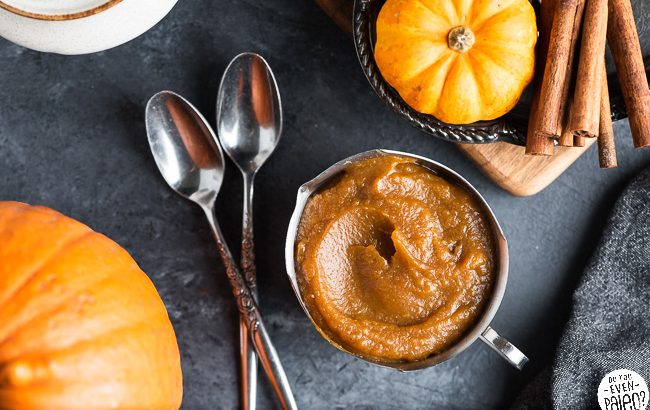 Serving dish filled with pumpkin butter, surrounded by spoons, pumpkins, and cinnamon