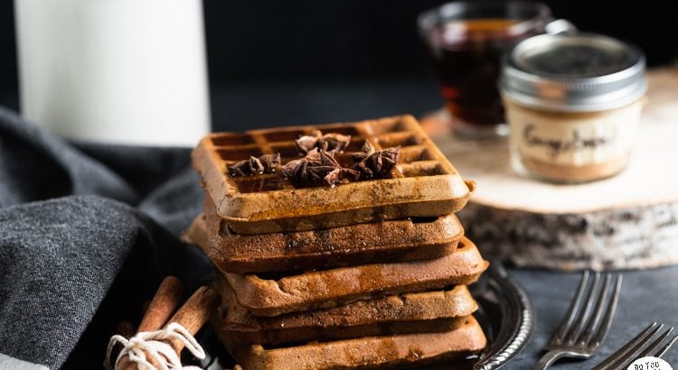 Stack of gingerbread waffles on a vintage plate, garnished with star anise and cinnamon sticks