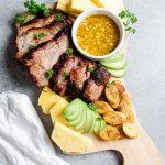 Smoked pork platter with pineapple, avocado, plantains, and mojo sauce