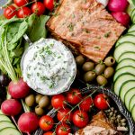 Dish of herbed whipped goat cheese dip on a grazing board with veggies and smoked salmon