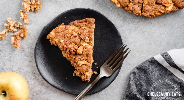 Slice of gluten free apple snack cake on a black dessert plate