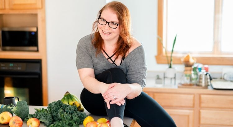 Woman sitting on a kitchen counter with produce around her