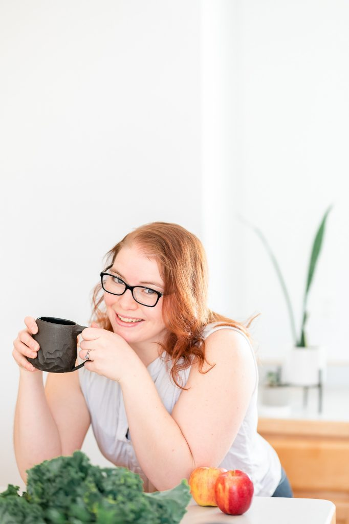 Woman in a white shirt holding a coffee cup and leaning on a kitchen counter