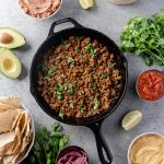 Overhead view of a skillet of taco meat with toppings surrounding it