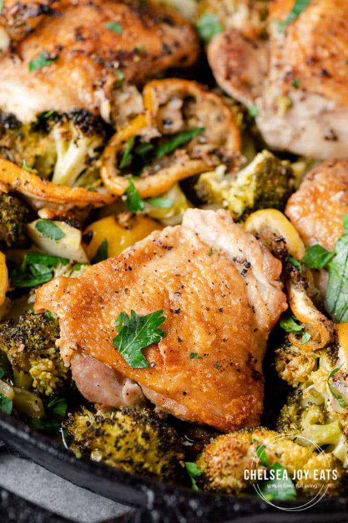 Closeup of roasted chicken thighs with broccoli and lemon