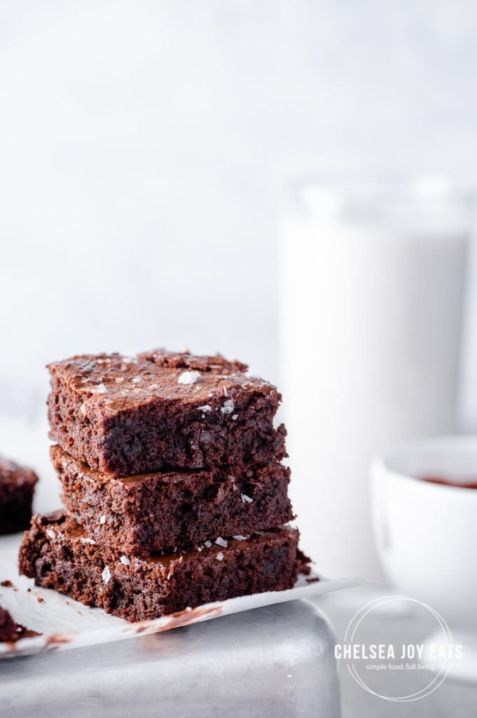 Stack of gluten free brownies with a glass of milk in the background