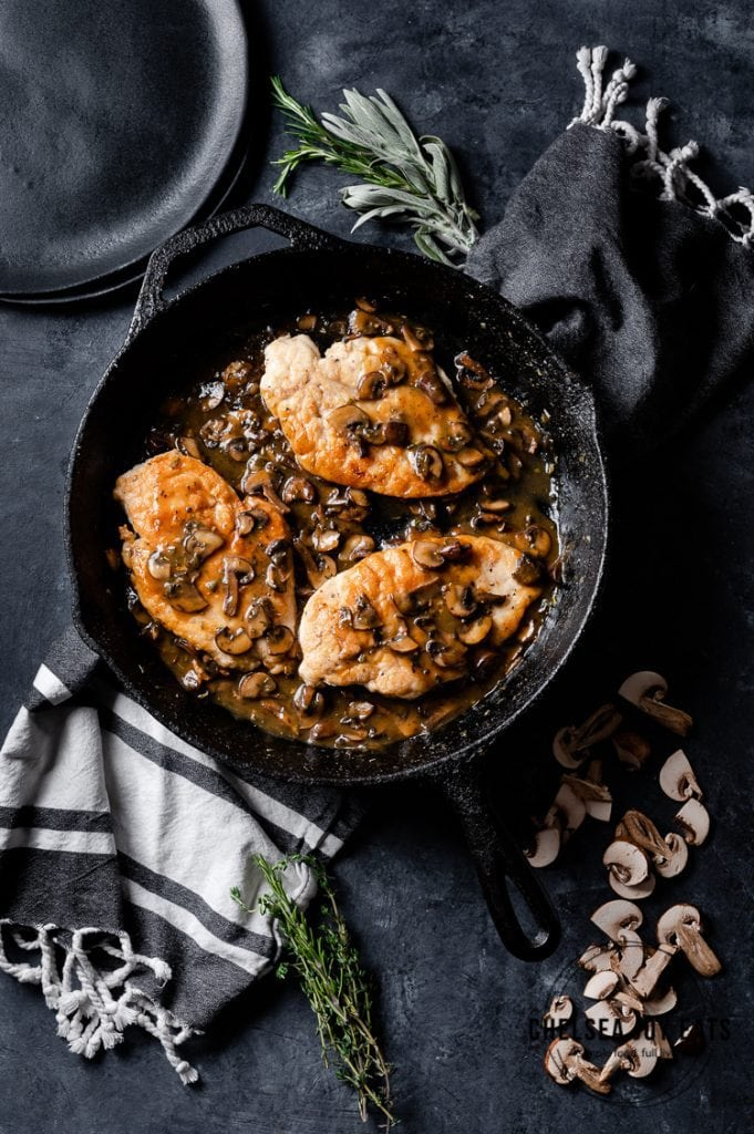 Cast iron skillet with chicken cutlets and mushroom sauce