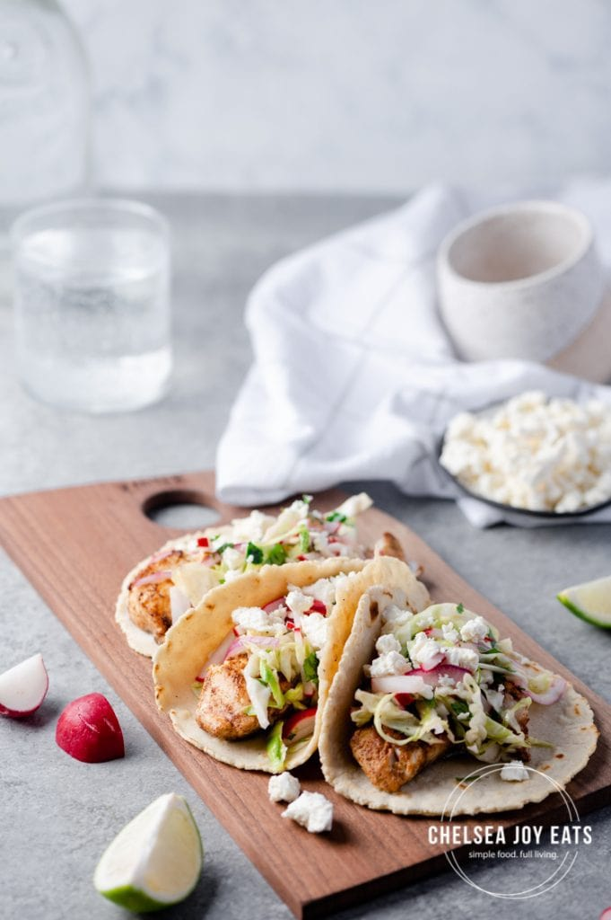 Fish tacos arranged on a board and garnished with radish slaw and cotija cheese
