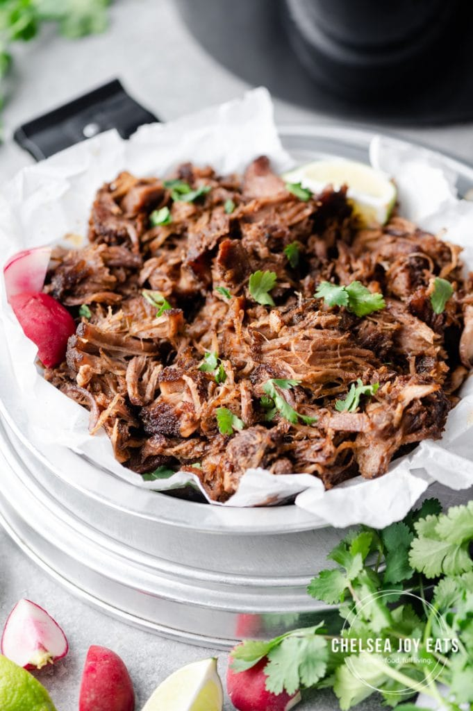 Closeup of easy pulled pork in a tray and garnished with parsley, limes, and radishes