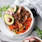 Pulled pork burrito bowls with grilled peppers, onions, rice, and avocado