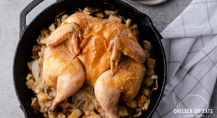 Butterflied roast chicken over potatoes and onions in a skillet