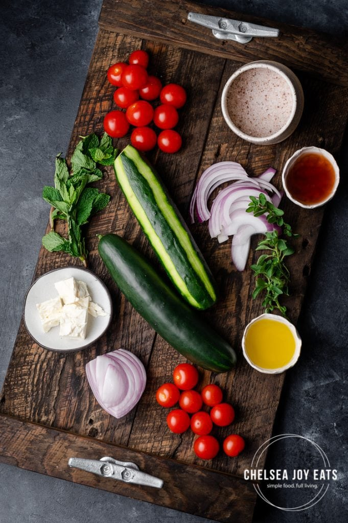 Fresh vegetables and herbs for a tomato and cucumber salad laid out on a wooden tray
