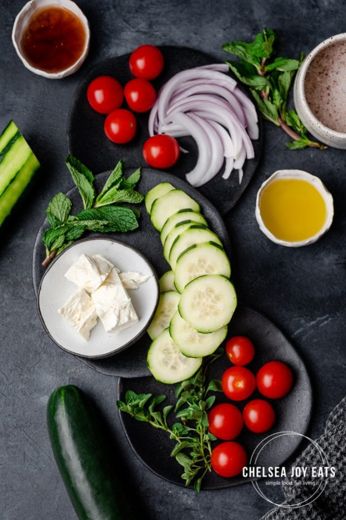 Fresh vegetables and herbs laid out on a dark background