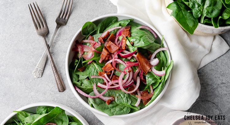Spinach with red onion and bacon in a white ceramic bowl