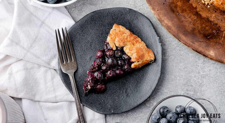 Slice of blueberry galette on a black plate